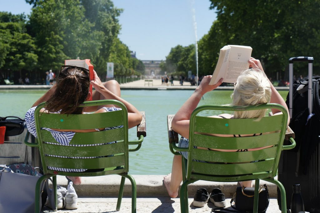 two women sitting on green chairs