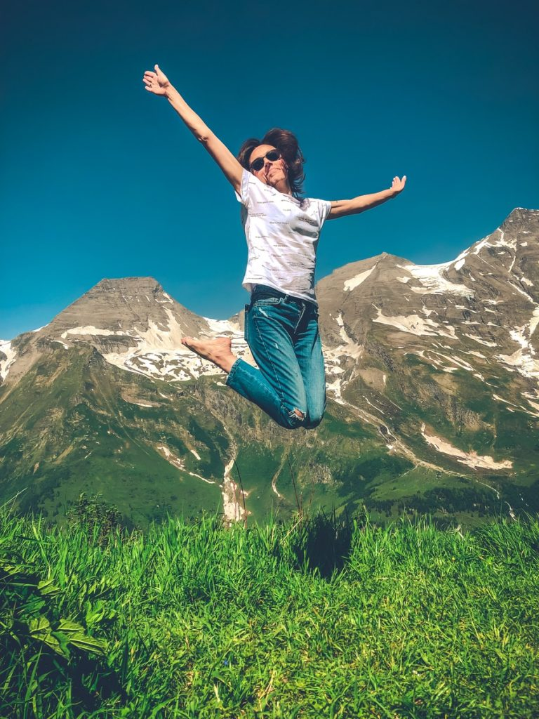 woman in white shirt and blue denim jeans jumping on green grass field during daytime